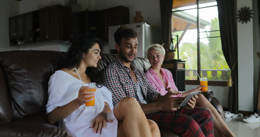 People Use Tablet Computer On Coach Watching Tv In Living Room Drink Juice, Young Man And Woman Group In Morning Talking Modern Apartment Interior Slow Motion 60 | Shutterstock HD Video #29315821