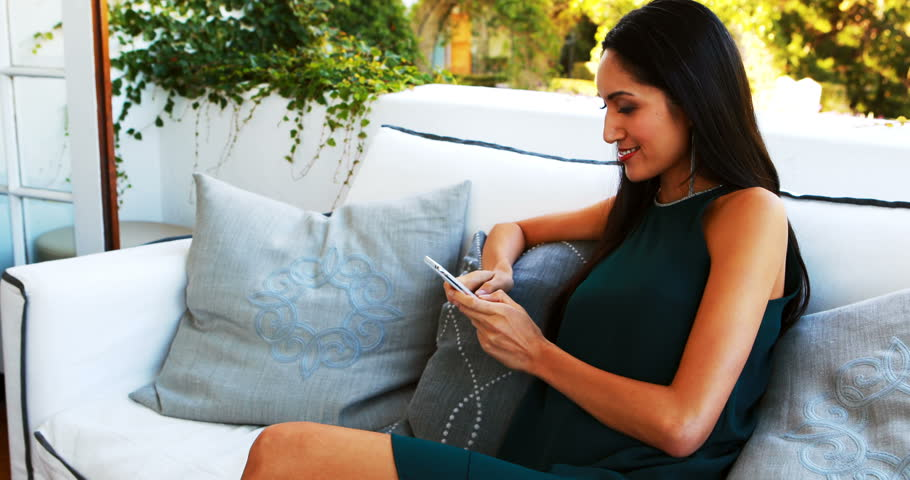 Beautiful woman sitting on sofa and using mobile phone in resturant