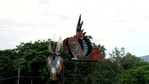 """A beautiful garden decorative instrument, the wind vane or weather vane with a propeller / turbine, a rooster and a money bag with Thai character write """"rich"""" on it."""