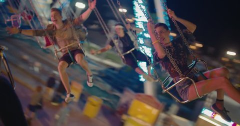 Happy teenage best friends riding the chairoplane carousel and having fun at the funfair