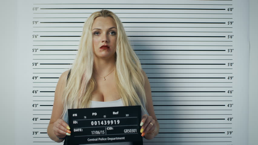 In a Police Station Arrested Woman Posing for Side, Front-View Mugshot. She Chews Gum, Wears Saucy Clothes, Has Smudged Heavy Makeup, Her Hair Is Disheveled and SHe Holds Placard.Height Chart on Wall