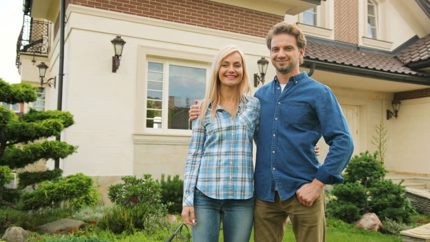 young attractive couple hugging and smiling on camera in front of new house 4k