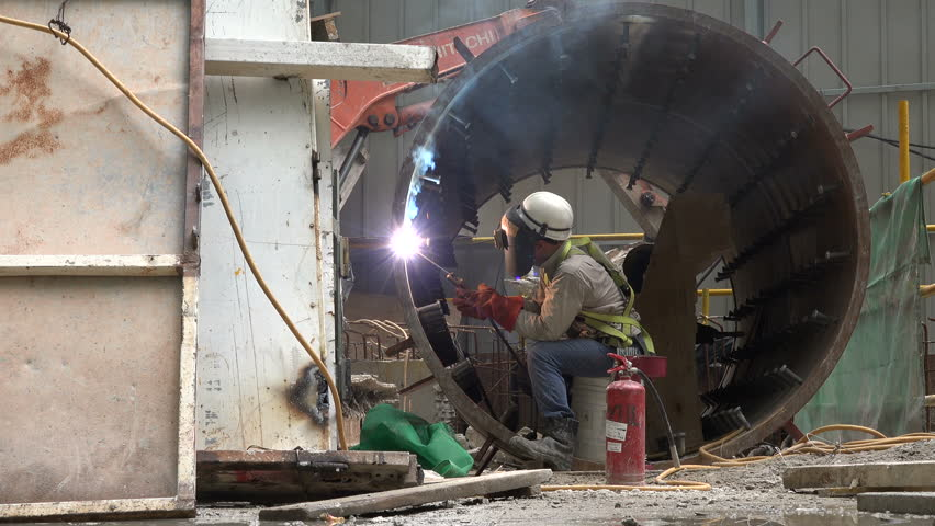 SINGAPORE - MAY 2017: Indian migrant worker welds inside tube on a construction site in Singapore