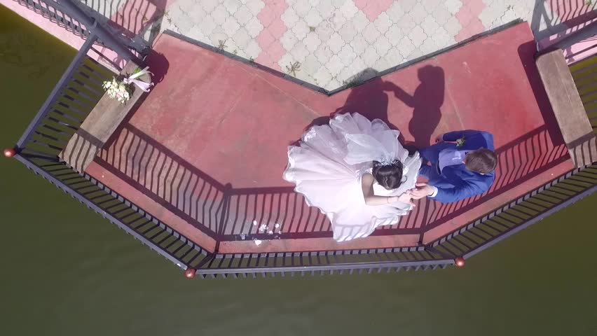 Bridge to the pond, top view, Bride dance bridesmaids in wedding costumes