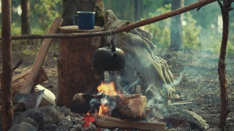 Idyllic camping scene with blue enamel mug, backpack, an axe and tea pot boiling over open fire medium shot