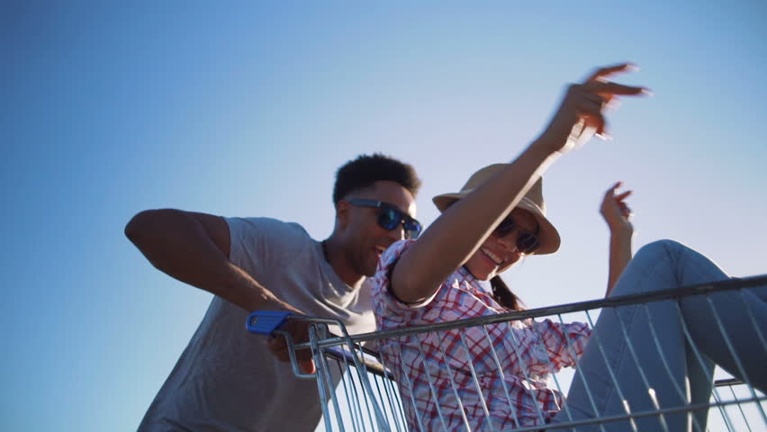 Young friends having fun on shopping trolleys. Multiethnic young people racing on shopping cart. slow motion