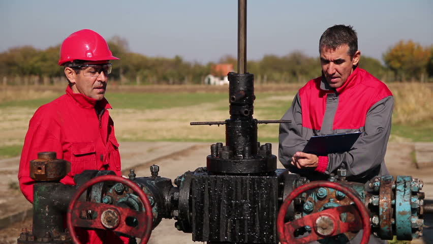 Oil Workers at Well Pump Jack Site. Oil and Gas Industry.  Engineer giving orders to oil worker next to pump jack. Power and energy.