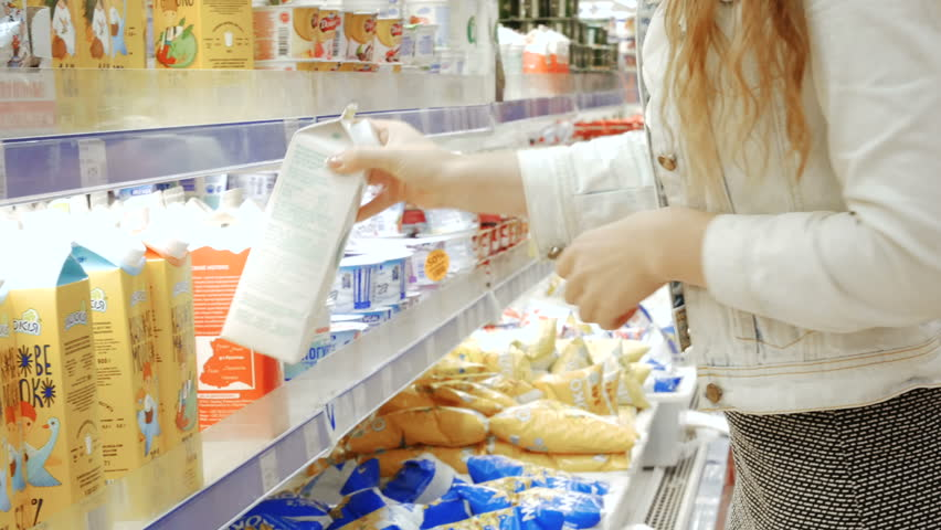 TERNOPIL, UKRAINE - JULY 15, 2017: Young woman in a dairy section of supermarket get a milk   Shutterstock HD Video #29430286