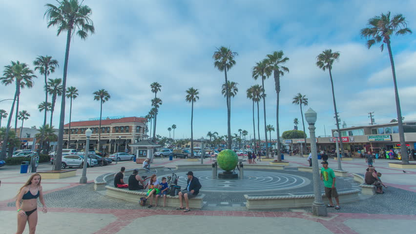Time-lapse or hyper lapse at Newport Pier entrance in Newport Beach, California with clouds racing overhead and palm trees, tourists and cars in the background.