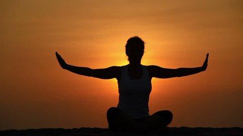 Healthy woman meditating in pose lotus over orange sun