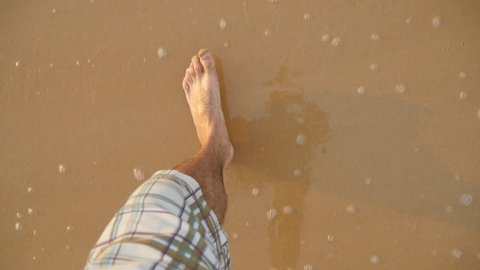 Point of view of young man stepping at the golden sand at sea beach. Male legs walking near ocean. Bare foot of guy going on sandy shore with waves. Summer vacation or holiday Slow motion Close up POV