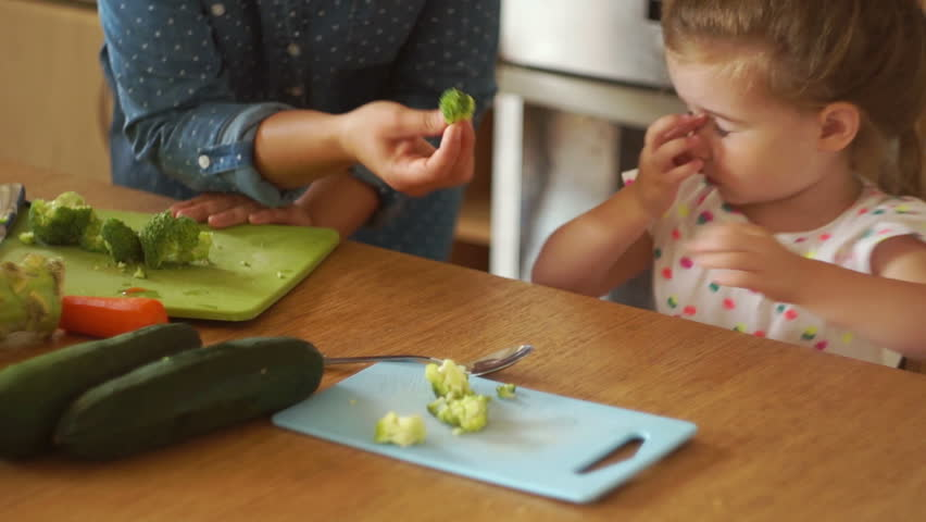Portrait of a little girl in the kitchen. Mom gives the daughter a broccoli and a carrot. The girl pushes the vegetables away. Healthy food. Childish whims.