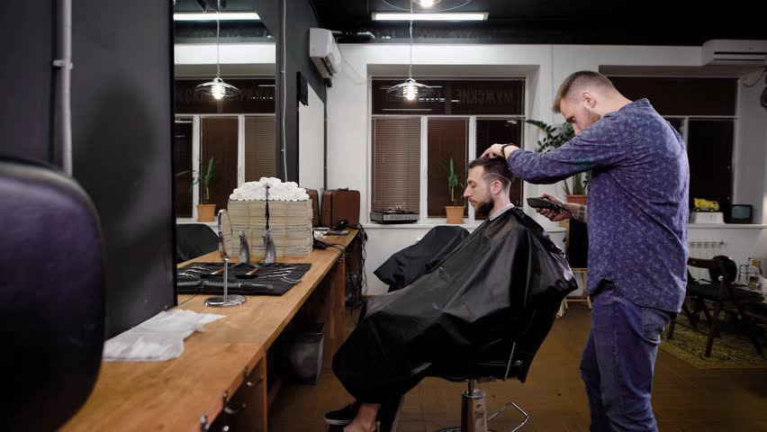 Young barber walking around armchair and doing haircut with clipper in the barbershop. Bearded man is sitting on the chair covered with black peignoir in the hairdressing saloon.