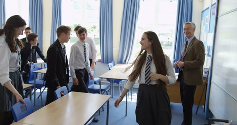 4K Tracking shot of happy students leaving classrooms in groups & walking through school building