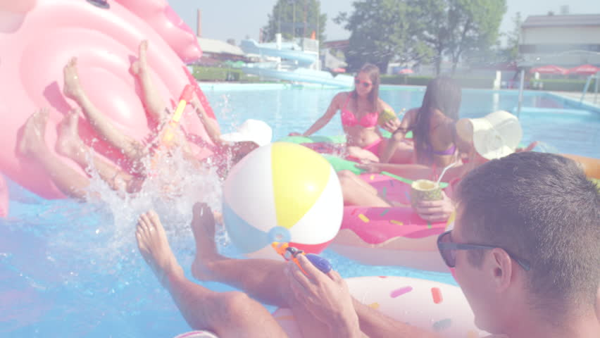 SLO-MO CLOSEUP: Smiling young couple falling off colorful floaties at pool party. Happy teenagers having watergun fight splashing water on inflatable pizza, flamingo, watermelon and doughnut floats