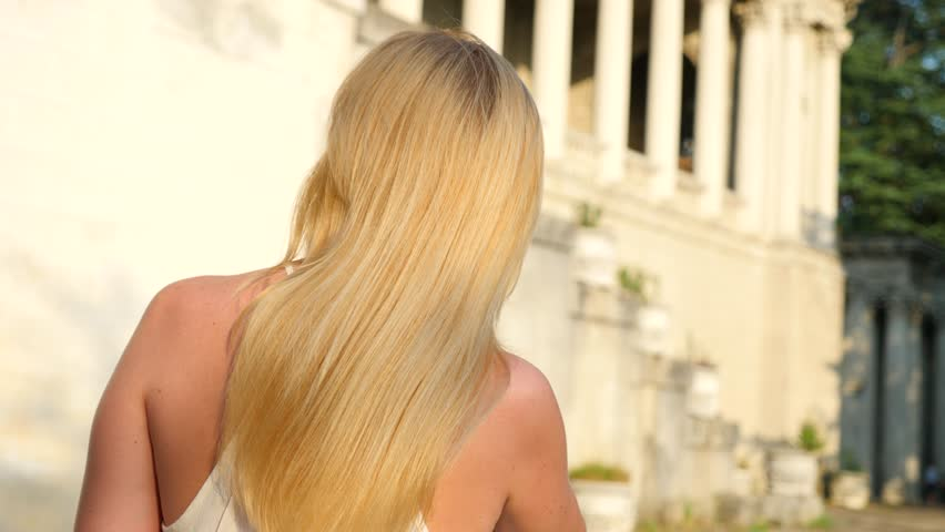Beautiful woman styling hair outdoors. Slow Motion. Happy calm attractive girl with long healthy hair having fun in the park, enjoying nature, playing with the wind. Close up. 4k | Shutterstock HD Video #29509564