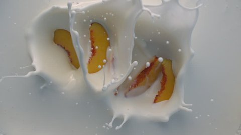Top View of Peach Falling into White Yogurt with Splashes