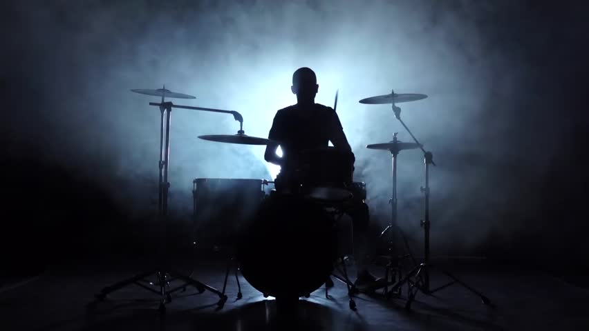 Energetic music in the performance of a professional drummer. Black background. Silhouette. Slow motion