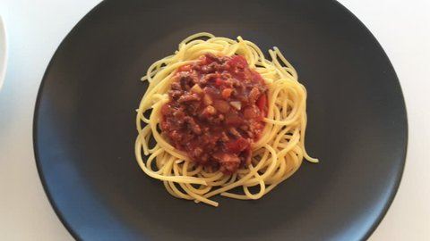 Classic homemade Spaghetti Bolognese cooked ingredients inside kitchen cooking utensils and equipment and Spaghetti Bolognese meal served in a plat.