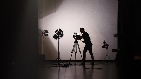 Working Behind the Scenes in Film Studio: Silhouette of Anonymous Cameraman Using Camera