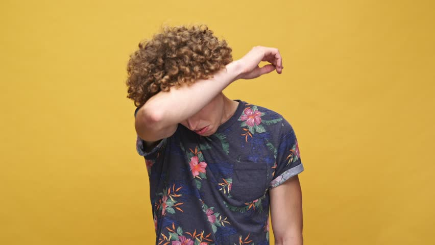 Young curly man in a t-shirt suffering from heat isolated over yellow background | Shutterstock HD Video #29585056