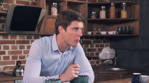 Young man eating cornflakes with milk for breakfast in the kitchen. Caucasian student relish meal and thinking or planning day. Handsome guy wearing casual clothes in the morning at home.