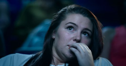 Close up of a frightened woman sitting in a movie theatre struggling to watch a scary movie.