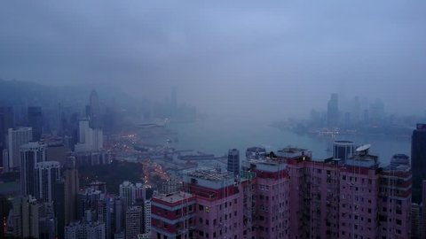 Dusk Hong Kong Island aerial cityscape at early morning, apartment complex on foreground, slide camera motion. Low clouds over Victoria Harbour, city shores silhouetted view at distance