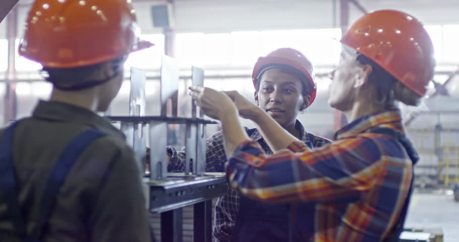 Slowmo of female factory worker in hardhat explaining her colleagues how to use caliper for measuring metal detail