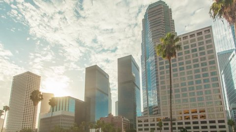 Cinematic 4K downtown Los Angeles city high rise buildings. Motion timelapse or hyperlapse at sunrise with fast moving clouds above and palm trees.
