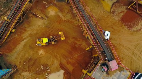 Excavator loader in sand quarry. Aerial view dumper trucks with cargo sand rides moving on territory sand factory. View from above sand work