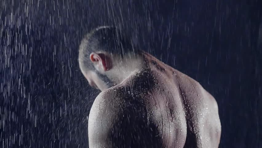 Nude male bodybuilder with big muscles back to camera stands in the shower in the darkness under the water jets. in his powerful big body flow water jet washing and removing fatigue training