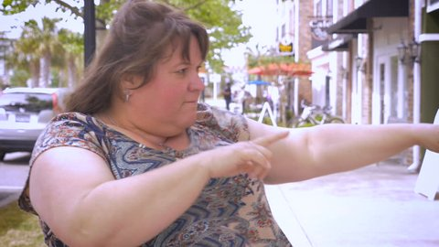 Close up of curvy woman dancing and having fun in the streets in outdoor shopping district in slow motion