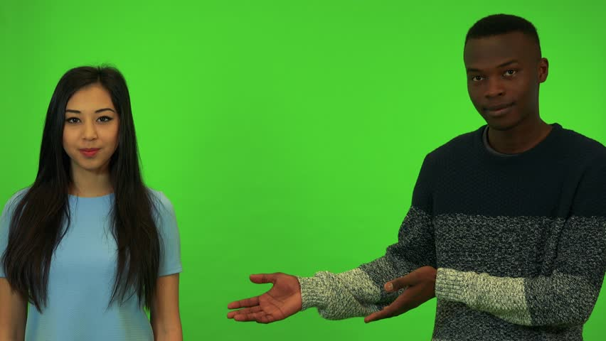 A young Asian woman and a young black man present something - green screen studio | Shutterstock HD Video #29689282