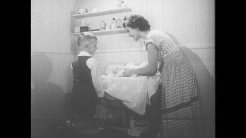 1950s: Boy helps put baby powder on baby. Dad reads bedtime story to boy. Mother lifts baby out of high chair. Boy walks in with bow. Mother puts baby back in high chair.