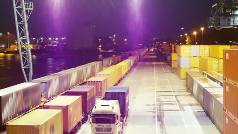 Container loaded by huge computer driven crane to Truck at a harbor at night.