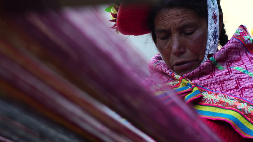 Peruvian woman weaving colorful alpaca wool in Peru