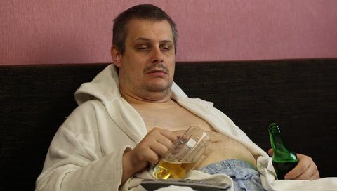 Drunk man asleep with a beer in his hands