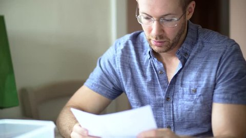 A man in debt is worried and stressed whilst looking through bill letters. Sad and anxious he holds his head in hands. White Caucasian wearing glasses in 30's.