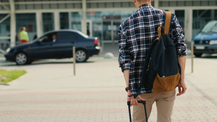 Young man walking to the modern airport terminal for his flight. View from the back. | Shutterstock HD Video #29743096