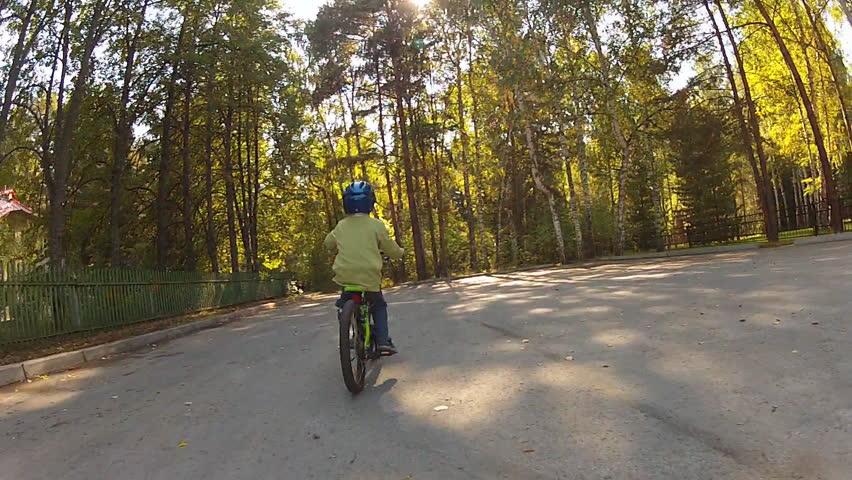 Little boy in a helmet riding on a bike. Back view.