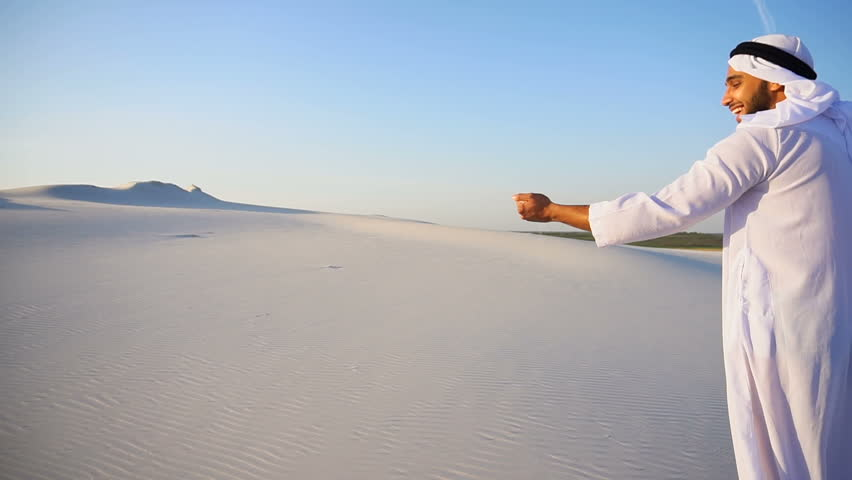 slowmotion Happy young Emirati Sheikh bends over and takes white sand in hands, rises up and lets sand through fingers of hands in slow motion, smiling on face, standing in midst of bottomless desert