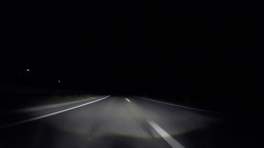 driving car in fast lane at night on highway with adaptive headlights