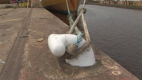 Close up of white iron bollard on dock tied to the recovery vessel Odyssey Explorer docked in Hull, England