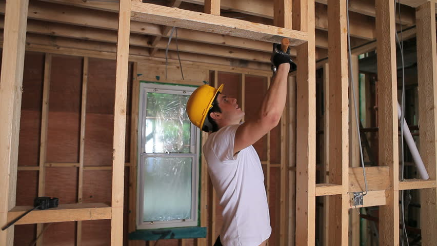 Builder hammering door frame in house construction site