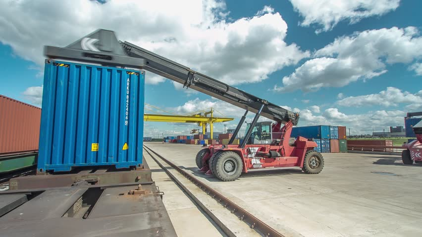 timelapse gantry crane and reachstacker unload freight containers from platforms on container yard