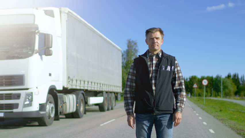 Professional Driver Gets out of the Parked White Semi Truck with Cargo Trailer Attached. Driver Stands in the Middle of the Road and Proudly Crosses Arms. Shot on RED EPIC-W 8K Helium Cinema Camera.