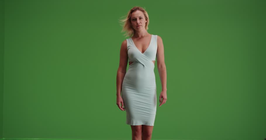 Sexy white woman in a tight dress walking toward the camera on green screen. On green screen to be keyed or composited.