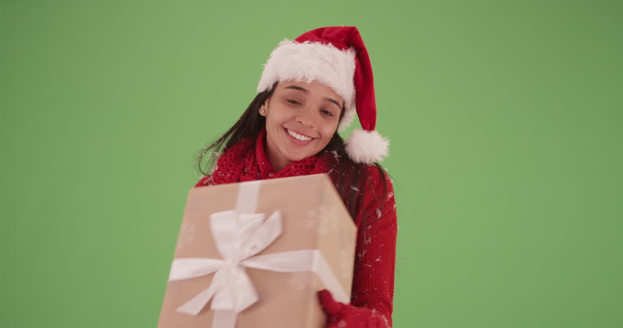 Playful Hispanic girl with a present in a red sweater on green screen. On green screen to be keyed or composited.