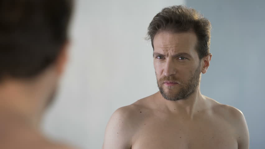 Middle-aged man looking in mirror at his bald patches, hair loss problem. Male feeling sad of appearance insecurities, bachelor health and body care, cosmetology beauty. Genetic predisposition, crisis | Shutterstock HD Video #29810806